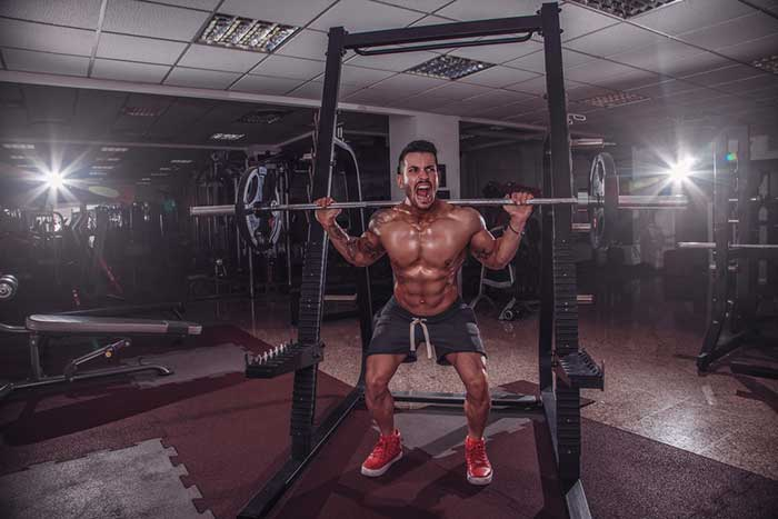 Man with muscle soreness doing squats
